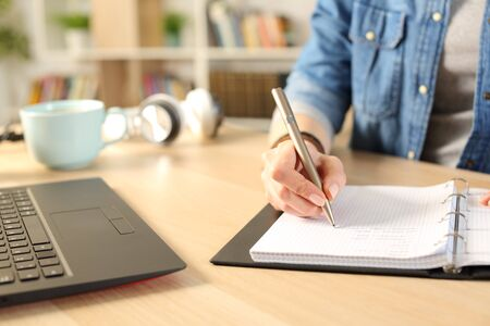 Close up of student girl hands writing on notebook on a desk at home