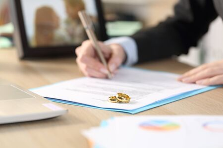 Close up of self employed woman hands divorcing signing papers on a desk at home office