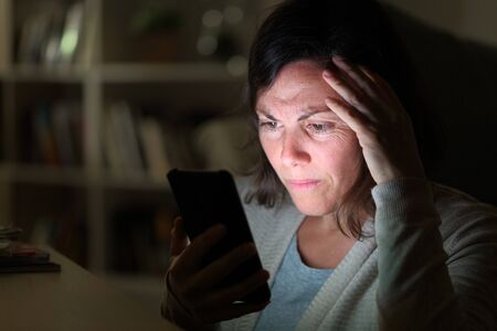 Preoccupied adult woman reading on smart phone lighted screen sitting at night at home