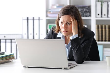 Worried adult executive woman reading news on laptop sitting on a desk at the office Фото со стока