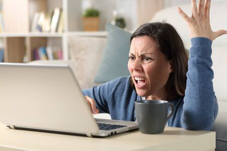 Angry adult woman watching video online on laptop sitting on the floor at home Stock Photo