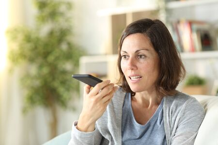 Adult woman using voice recognition system on smart phone sitting on a couch at home Banco de Imagens