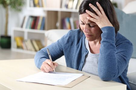 Sad middle age woman signing document complaining sitting in the living room at home