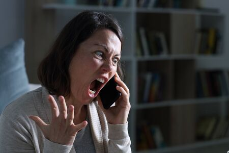 Angry adult woman screaming calling on smart phone sitting in the livingroom at night at home
