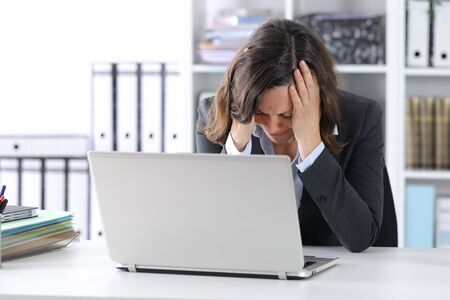 Sad adult executive woman with laptop complaining sitting on a desk grabbing her head at the office Фото со стока