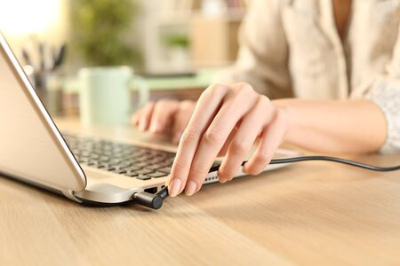 Close up of woman hands plugging battery charger on laptop at home