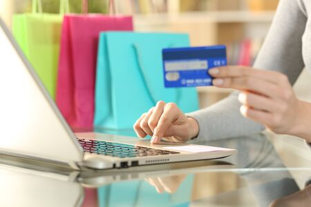 Close up of shopper woman hands buying with credit card on laptop on a desk at home with bags on the background