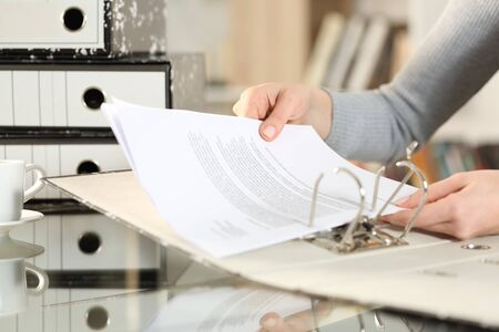 Close up of woman hands organizing documents putting files on folder on a desk at home