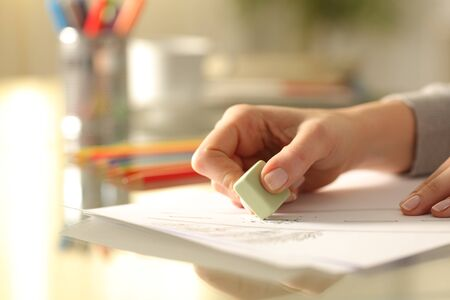 Close up of woman hands erasing drawing with rubber on desk at home