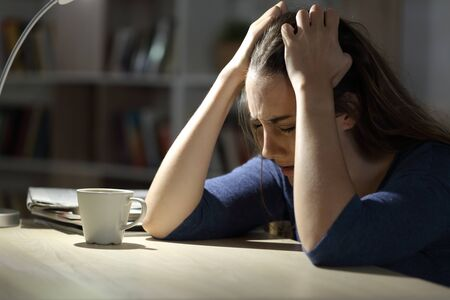 Sad woman complaining at night grabbing head sitting alone at home