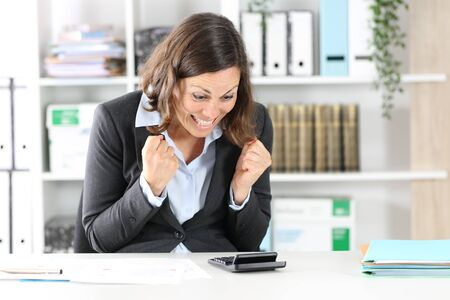 Excited adult executive woman celebrating checking result on calculator sitting on a desk at office
