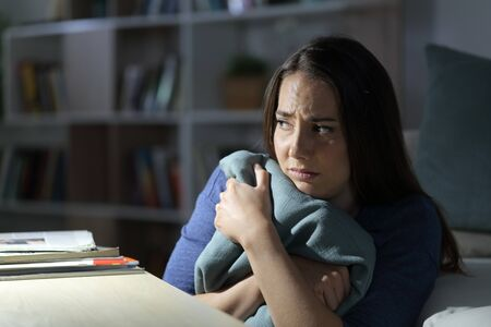 Scared woman looking away sitting alone in the night in the living room at home
