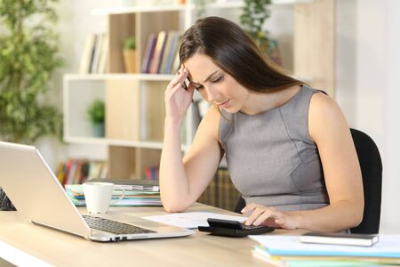 Worried bookkeeper woman calculating on calculator sitting on a desk at homeoffice