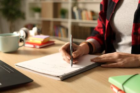 Close up of student hand taking notes on notebook at night on a table in the living room