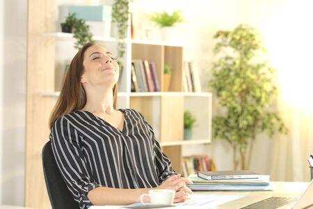 Happy entrepreneur woman breathing fresh air sitting on a desk at homeoffice