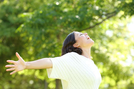 Happy adult woman breathing fresh air outstretching arms in the park at summer