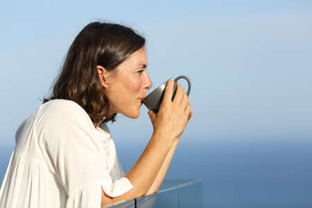 Side view portrait of a happy adult woman drinking coffee cup standing in a balcony on the beach