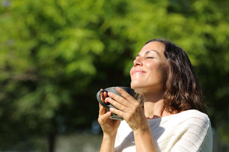 Satisfied adult woman smelling coffee cup standing in a green park at summer