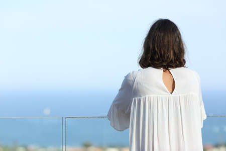 Back view of an adult woman contemplates beach views on a hotel balcony at summer
