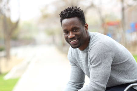 Happy black man posing looking confident at camera sitting outdoors on a park