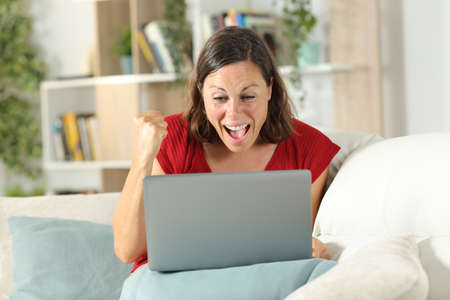 Excited adult lady celebrates good news on laptop sitting on a couch at home