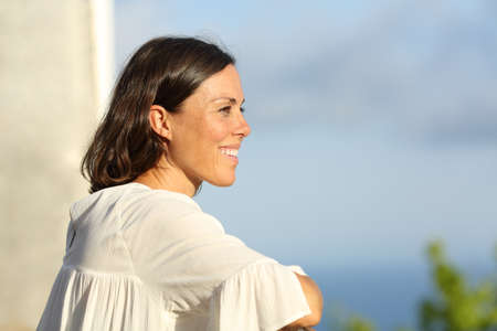Mid aged woman contemplating views from a hotel balcony on summer vacation