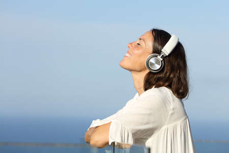 Adult woman breathing fresh air relaxing listening to music with headphones in a hotel balcony on the beach