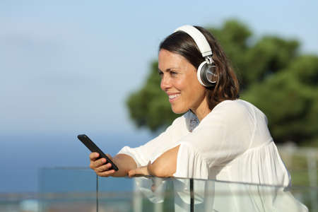 Happy adult woman with headphones listens music on a smart phone on a balcony at the beach