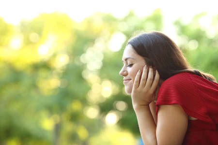 Profile of a relaxed woman meditating with closed eyes sitting in a park