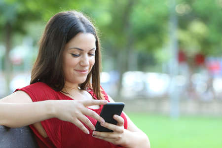 Smiley woman in red checks smart phone sitting on a bench in a park