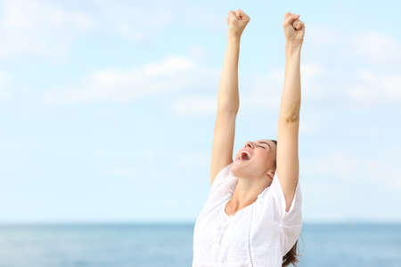 Excited woman celebrating raising arms and screaming on the beach on summer Stock Photo