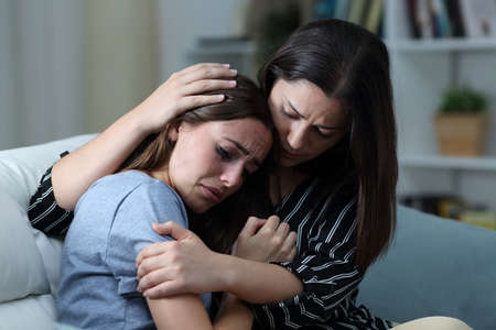 Sad teen crying being comforted by her sister on a couch in the living room at home Stockfoto
