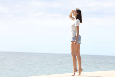Full body profile of a beautiful woman with beautiful long legs looking away on the beach