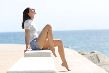 Profile of a happy woman with long waxed legs breathing fresh air sitting on a bench on the beach
