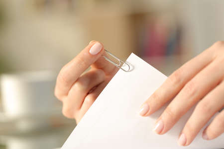 Close up of a woman hands putting a paper clip on a sheet at home Banque d'images