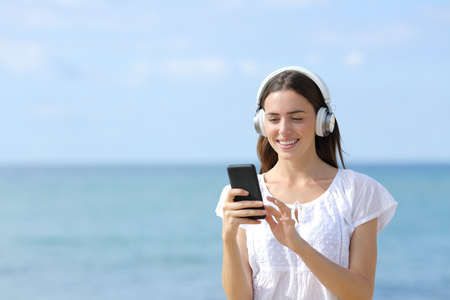 Happy woman wearing headphones listening to music from smart phone on the beach
