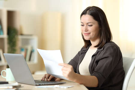 Woman reading a letter using laptop sitting in a table at home Stockfoto