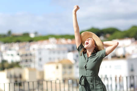 Excited tourist raising arm on summer vacation in a rural town a sunny day