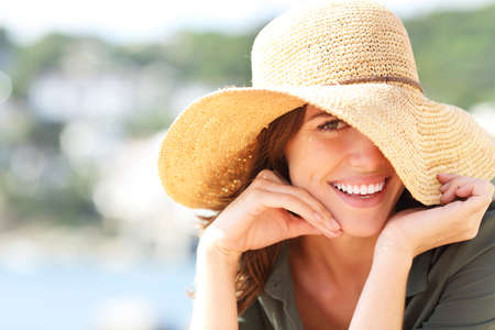 Portrait of a happy woman wearing pamela smiling with perfect teeth on summer vacation on the beach 写真素材