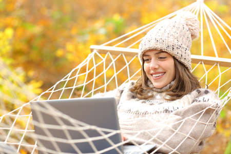 Happy woman lying on hammock using laptop in autumn in a forest