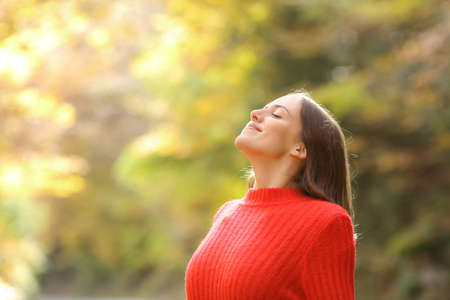 Satisfied woman in red breathing fresh air in autumn in a beautiful forest or park