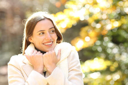 Portrait of happy woman looking away while holding her scarf in autumn at the park