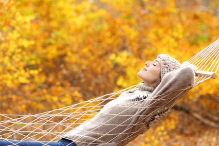 Side view portrait of a relaxed woman wearing sweater lying on a rope hammock in autumn in a beautiful forest