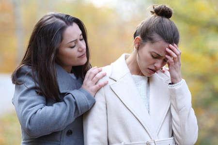 Woman comforting her sad best friend who is complaining in a park in winter