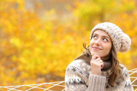 Pensive woman looks at side on a hammock in autumn in a forest Banque d'images