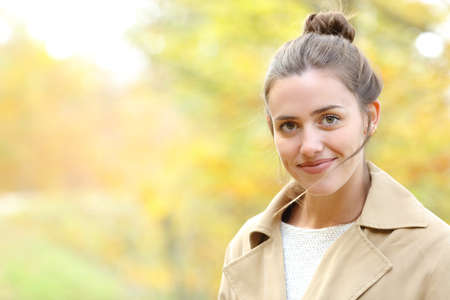 Portrait of a happy woman looking at camera in a park in autumn 写真素材