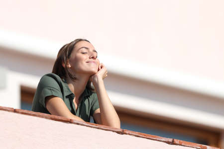 Happy woman breathing deep fresh air from balcony in apartment a sunny day