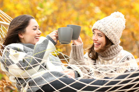 Two happy friends toasting with coffee cups in autumn holiday in a forest