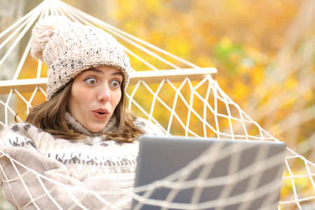 Amazed tourist lying on hammock checking surprising news on laptop in autumn in a forest