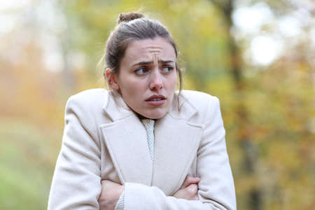 Angry woman getting cold complaining walking in winter in a park Stok Fotoğraf